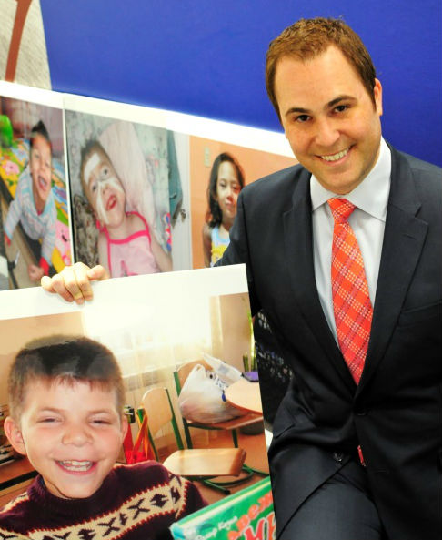 Michael Meltzer posing with a portrait of Yura, a Maya's Hope Cutie Pie. Photo credit: Jered Haag